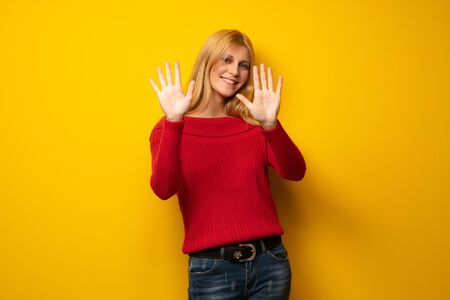 Blonde woman over yellow wall counting ten with fingers Stock Photo