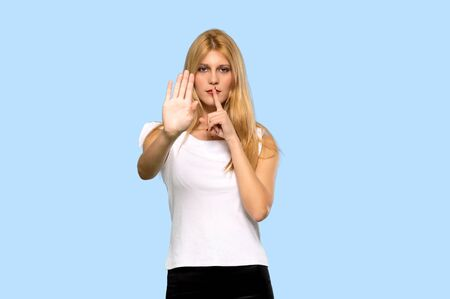 Young blonde woman making stop gesture denying a situation that thinks wrong on isolated blue background