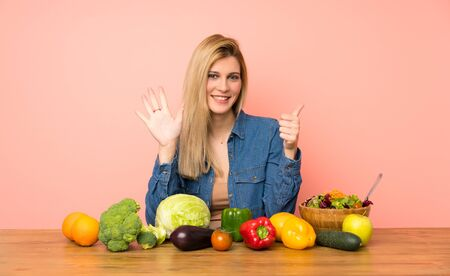 Young blonde woman with many vegetables counting six with fingers