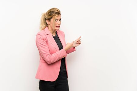 Young blonde woman with pink suit frightened and pointing to the side