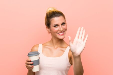 Young blonde woman holding a take away coffee saluting with hand with happy expression
