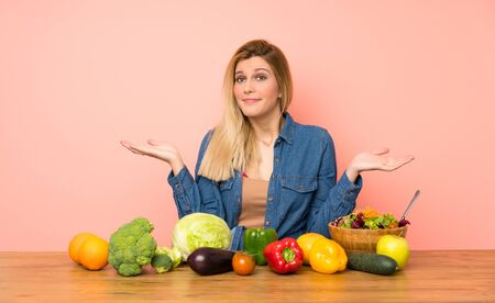 Young blonde woman with many vegetables having doubts while raising hands