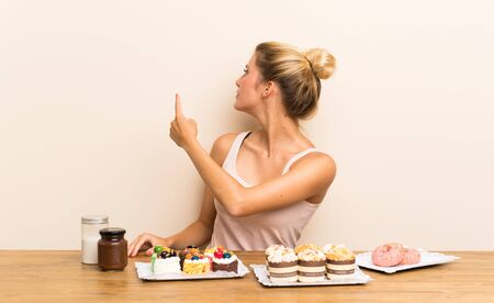 Young woman with lots of different mini cakes in a table pointing back with the index finger