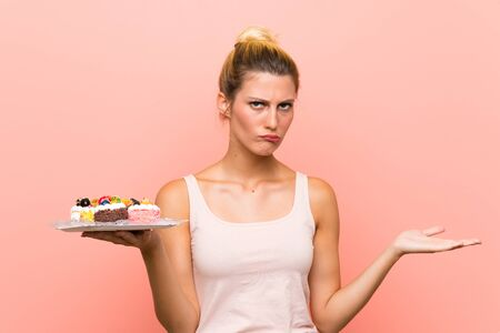 Young blonde woman holding lots of different mini cakes making doubts gesture while lifting the shoulders
