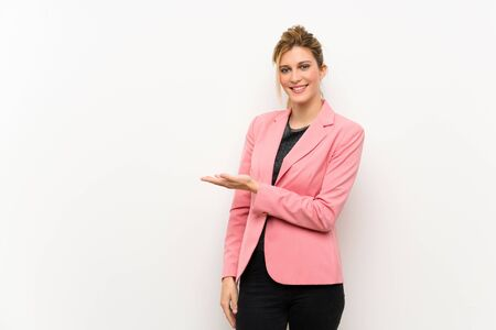 Young blonde woman with pink suit presenting an idea while looking smiling towards