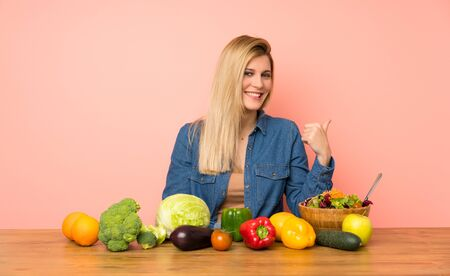 Young blonde woman with many vegetables pointing to the side to present a product Stock fotó