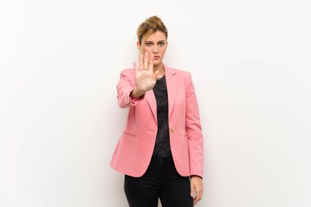 Young blonde woman with pink suit making stop gesture Stock fotó