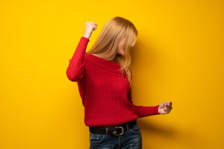 Blonde woman over yellow wall celebrating a victory