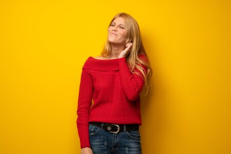 Blonde woman over yellow wall having doubts