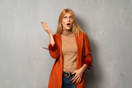 Woman over textured background surprised and shocked while looking right