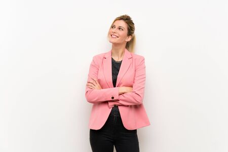 Young blonde woman with pink suit looking up while smiling