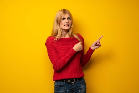 Blonde woman over yellow wall frightened and pointing to the side