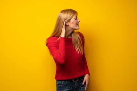 Blonde woman over yellow wall listening to something by putting hand on the ear