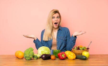 Young blonde woman with many vegetables with shocked facial expression
