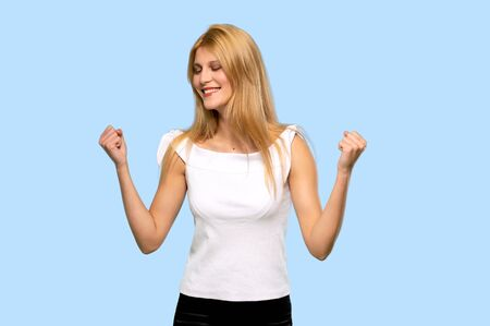 Young blonde woman celebrating a victory on isolated blue background