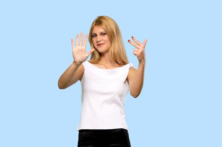 Young blonde woman counting eight with fingers on isolated blue background Zdjęcie Seryjne