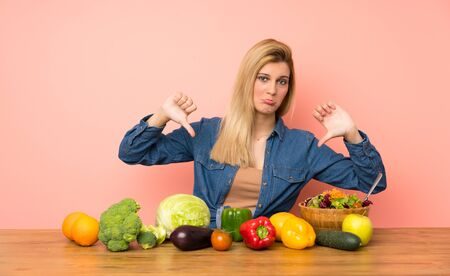 Young blonde woman with many vegetables showing thumb down