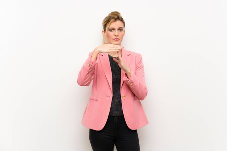 Young blonde woman with pink suit making time out gesture