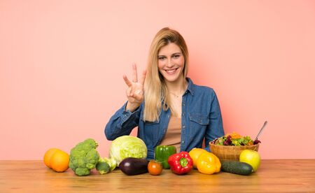 Young blonde woman with many vegetables happy and counting three with fingers Zdjęcie Seryjne