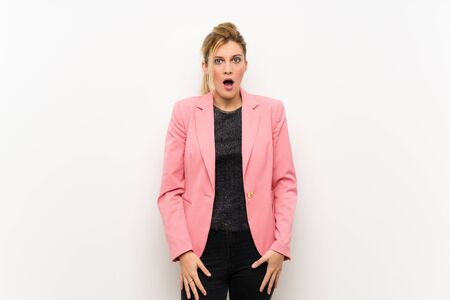 Young blonde woman with pink suit with surprise facial expression