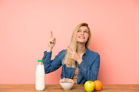 Young blonde woman with bowl of cereals pointing with the index finger a great idea Stock fotó