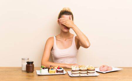 Young woman with lots of different mini cakes in a table covering eyes by hands