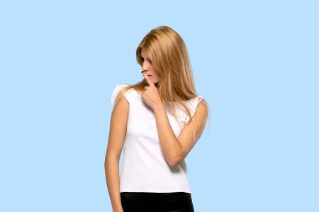 Young blonde woman having doubts and thinking on isolated blue background