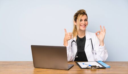 Blonde doctor woman showing ok sign and thumb up gesture