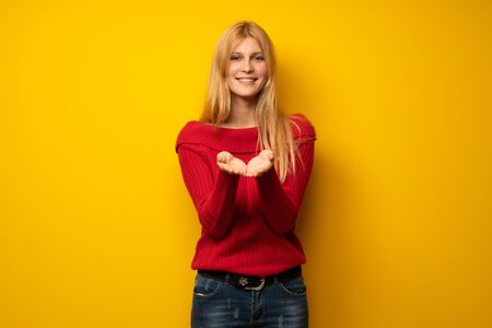 Blonde woman over yellow wall holding copyspace imaginary on the palm to insert an ad Stock Photo