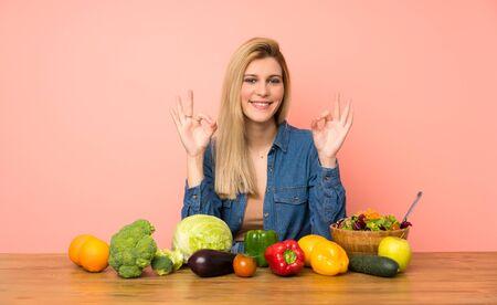 Young blonde woman with many vegetables in zen pose 版權商用圖片