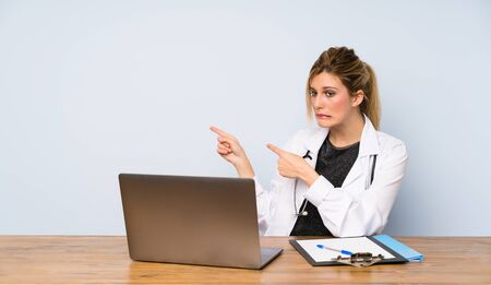 Blonde doctor woman frightened and pointing to the side