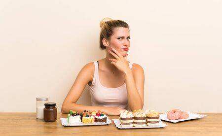 Young woman with lots of different mini cakes in a table thinking an idea Stock fotó