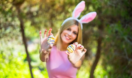 young blonde woman wearing bunny ears and with colorful Easter eggs Zdjęcie Seryjne