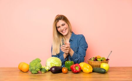 Young blonde woman with many vegetables applauding after presentation in a conference