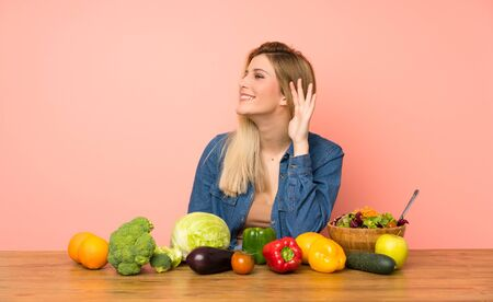 Young blonde woman with many vegetables listening to something by putting hand on the ear