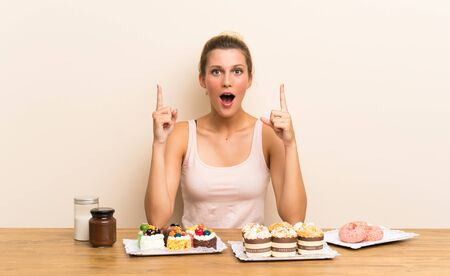 Young woman with lots of different mini cakes in a table pointing with the index finger a great idea