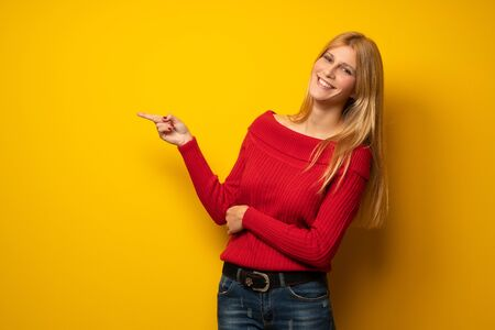 Blonde woman over yellow wall pointing finger to the side in lateral position
