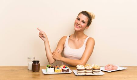 Young woman with lots of different mini cakes in a table pointing finger to the side