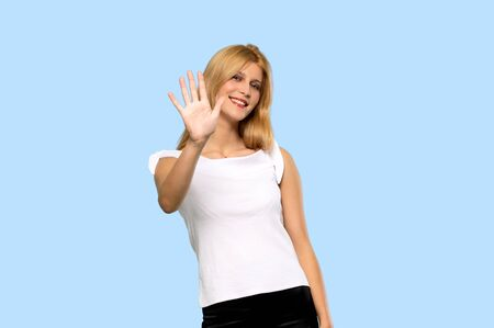Young blonde woman counting five with fingers on isolated blue background