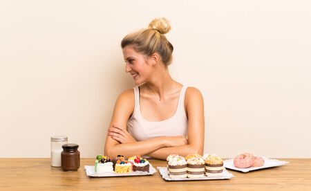 Young woman with lots of different mini cakes in a table looking to the side
