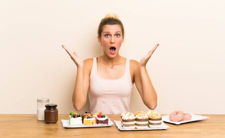 Young woman with lots of different mini cakes in a table with surprise facial expression Stock fotó - 130164048