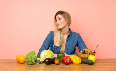 Young blonde woman with many vegetables making doubts gesture looking side