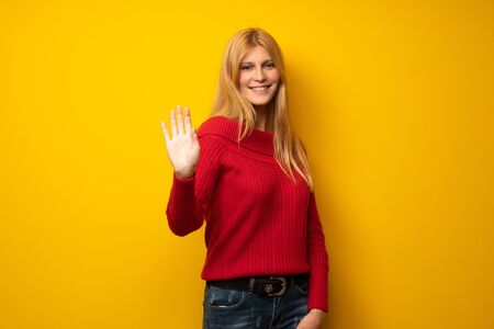 Blonde woman over yellow wall saluting with hand with happy expression