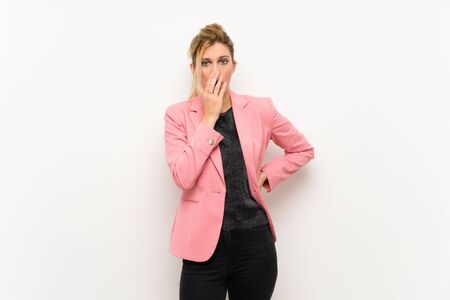 Young blonde woman with pink suit surprised and shocked while looking right