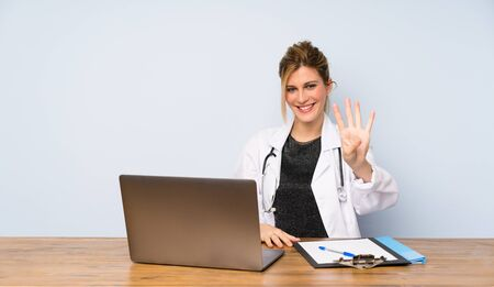 Blonde doctor woman happy and counting four with fingers Zdjęcie Seryjne
