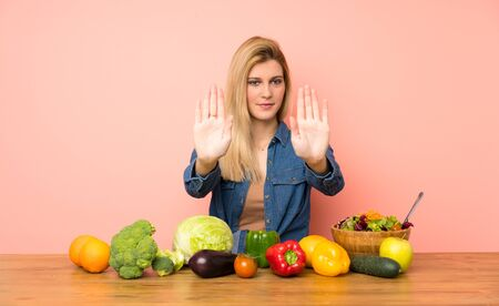 Young blonde woman with many vegetables making stop gesture and disappointed Stock fotó