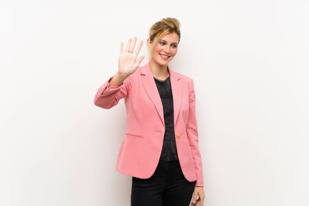 Young blonde woman with pink suit counting five with fingers