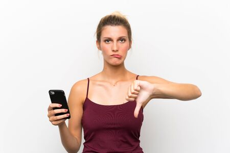 Young blonde woman using mobile phone showing thumb down sign