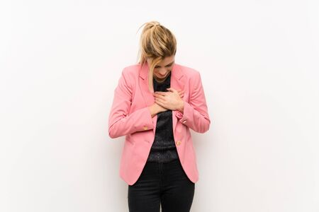 Young blonde woman with pink suit having a pain in the heart