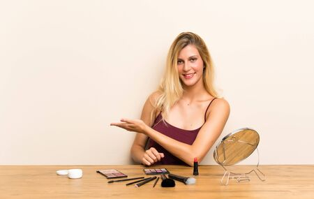 Young blonde woman with cosmetic in a table extending hands to the side for inviting to come